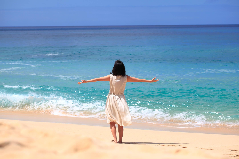 ハワイ州オアフ島のビーチで陽光を浴びる女性