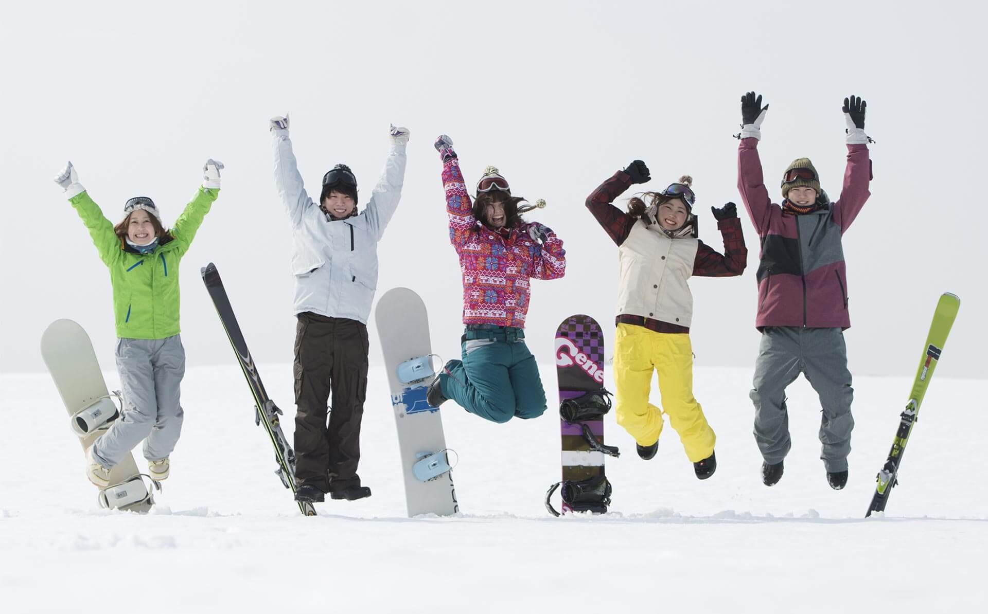 ゲレンデでジャンプをする若者たち